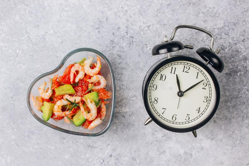 Intermittent fastin concept - countdown to eat. Diet. Healthy food. Intermittent fastin concept - countdown to eat salad with avocado, grapefruit and shrimps in stock photography