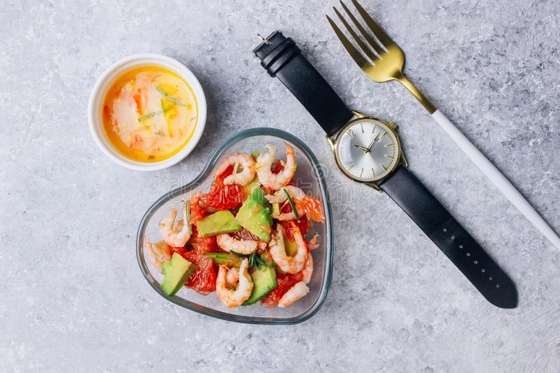 Intermittent fastin concept - countdown to eat. Diet. Healthy food. Intermittent fastin concept - countdown to eat salad with avocado, grapefruit and shrimps in royalty free stock images