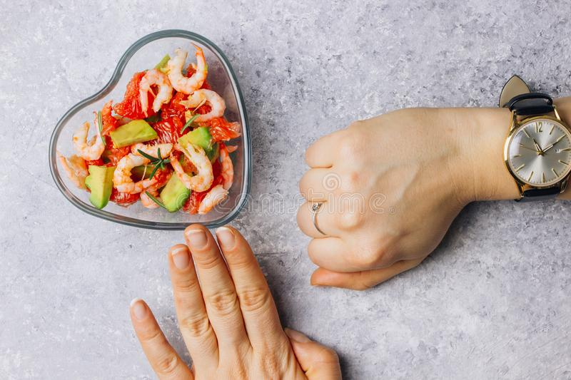 Intermittent fastin concept - countdown to eat. Diet. Healthy food. Intermittent fastin concept - countdown to eat salad with avocado, grapefruit and shrimps in royalty free stock image
