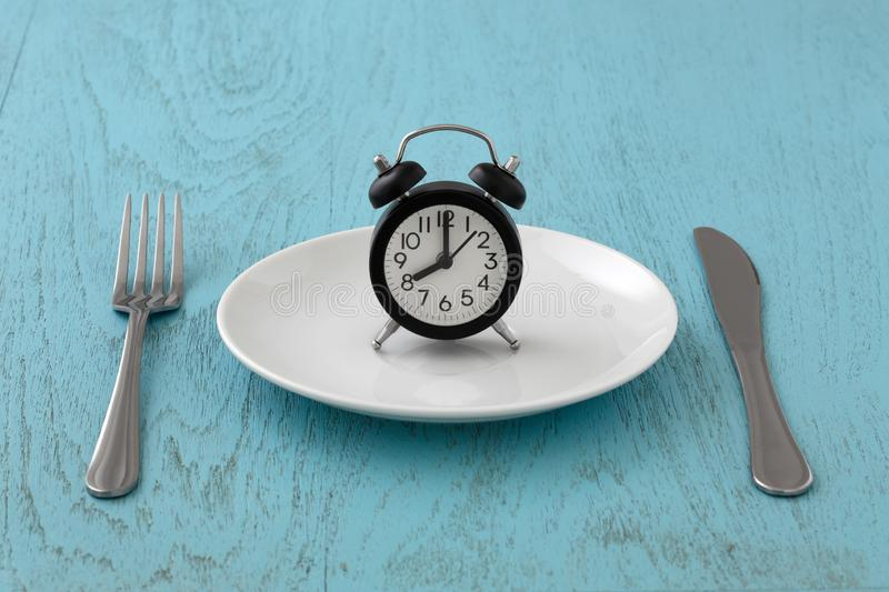 Intermittent fasting with clock on white plate. Clock on white plate with fork and knife, intermittent fasting, meal plan, weight loss concept on blue table royalty free stock photos