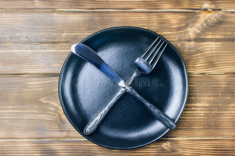 Intermittent fasting concept with empty black plate. Intermittent fasting concept with knife and fork showing cross symbol on black plate, top view royalty free stock image