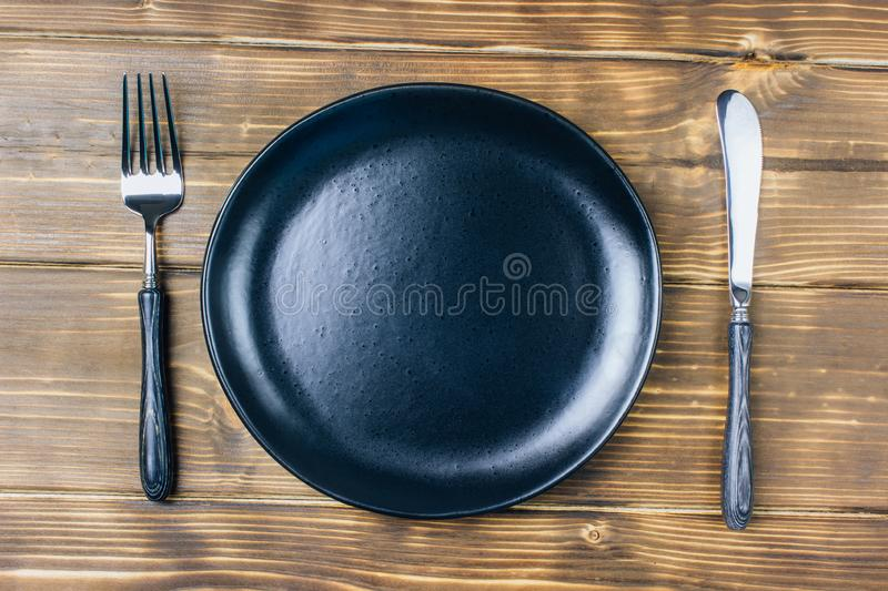 Intermittent fasting concept with empty black plate. Intermittent fasting concept with knife and fork, black plate with , top view stock photos