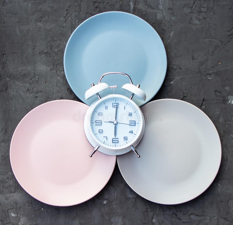 Intermittent fasting concept with empty colorful plates. Time to lose weight , eating control or time to diet concept. Intermittent fasting concept with empty royalty free stock photography