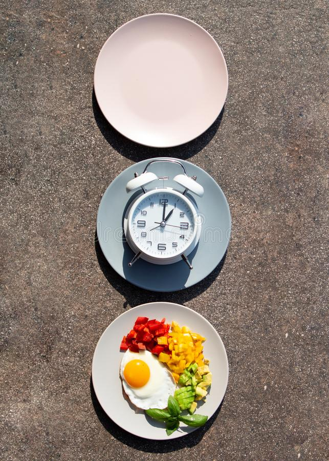 Intermittent fasting concept with empty colorful plates. Time to lose weight , eating control or time to diet concept. Intermittent fasting concept with empty stock images