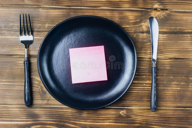 Intermittent fasting concept with empty black plate. Intermittent fasting concept with knife and fork, empty black plate with sticky note, top view royalty free stock image