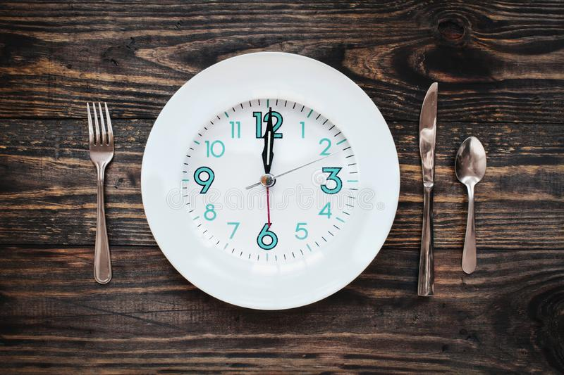 Intermittent Fasting Concept. Twelve hour intermittent fasting time concept with clock on plate over a rustic wooden table / background. Top view royalty free stock image