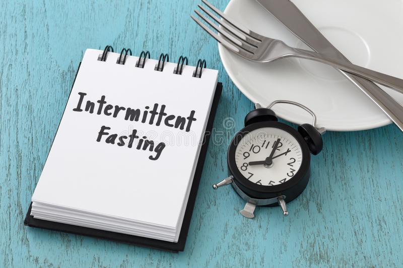 Intermittent fasting concept. Intermittent fasting word on notepad with clock, fork and knife on white plate, intermittent fasting and weight loss concept stock photos