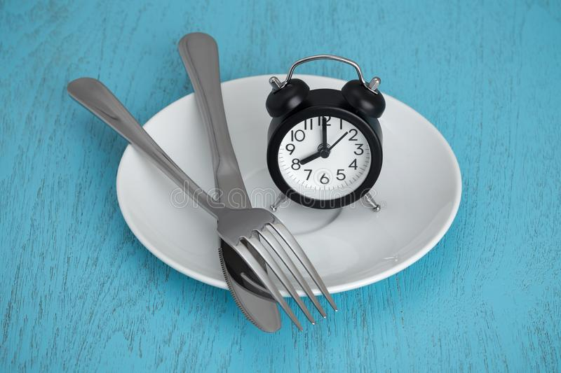 Intermittent fasting. Concept with clock on white plate, fork and knife on blue table stock photos