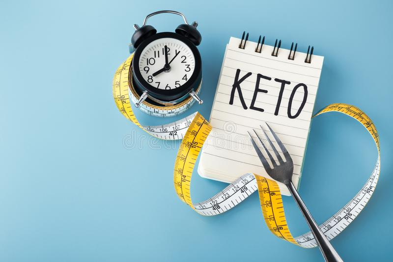 Intermittent fasting on keto on blue background. Intermittent fasting on keto concept on blue backgroun with copy space stock image
