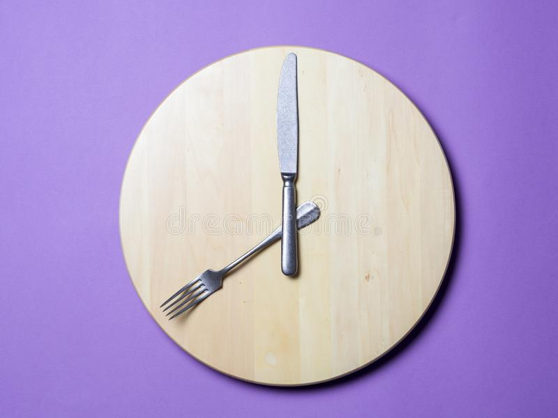 Intermittent fasting and skip breakfast concept. Empty wooden round tray or trencher with cutlery as clock hands on lilac background. Eight hour feeding stock photos