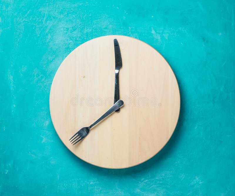 Intermittent fasting and skip breakfast concept. Empty wooden round tray or trencher with cutlery as clock hands on blue background. Eight hour feeding window royalty free stock photo