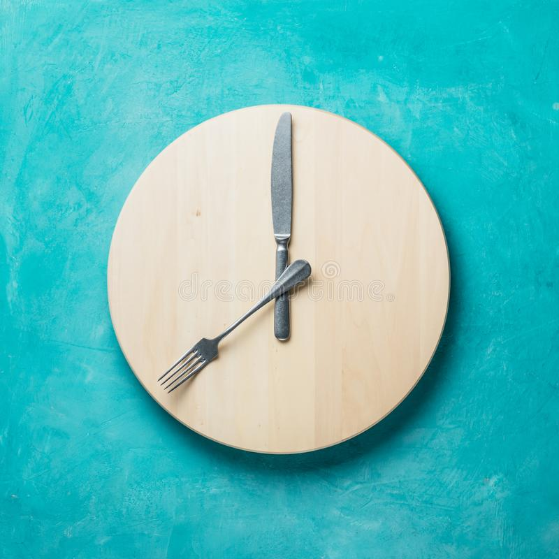 Intermittent fasting and skip breakfast concept. Empty wooden round tray or trencher with cutlery as clock hands on blue background. Eight hour feeding window royalty free stock images