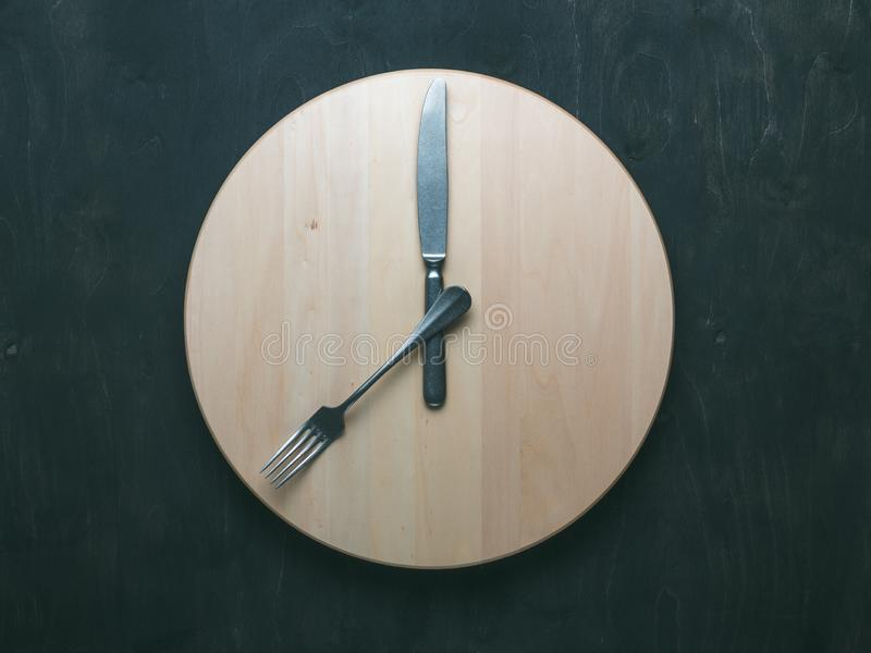 Intermittent fasting and skip breakfast concept. Empty wooden round tray or trencher with cutlery as clock hands on dark background. Eight hour feeding window stock photo