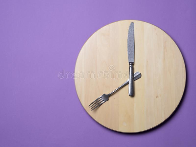 Intermittent fasting and skip breakfast concept. Wooden round tray or trencher with cutlery as clock hands on lilac background. Eight hour feeding window royalty free stock photography