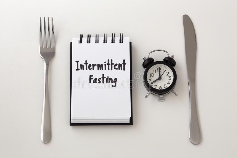 Intermittent fasting word on notepad with clock. Fork and knife, weight loss plan royalty free stock photography