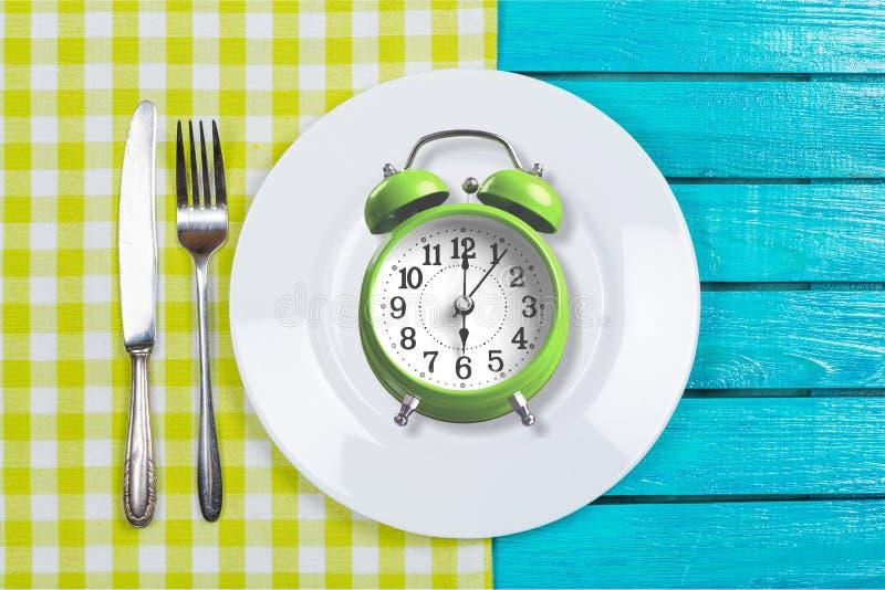 Intermittent. Fasting concept above breakfast clock delay stock photo