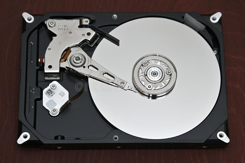 Computer hard disk-hard drive on an background. Internal parts of a hard disk on an braun,wood background royalty free stock image