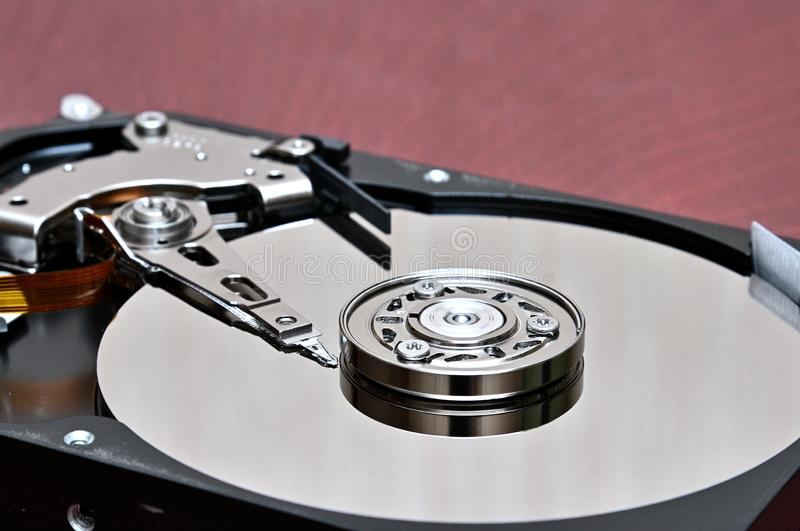 Computer hard disk-hard drive on an background. Internal parts of a hard disk on an braun,wood background stock images