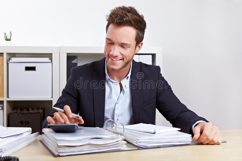 Internal revenue and tax audit. Man from internal revenue doing tax audit with calculator in office stock images
