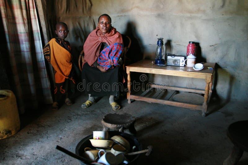Internal view of maasai hut, black woman and children indoors. stock photos