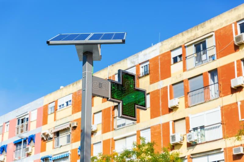 Internationaal groen dwarsneonteken voor apotheken met zonnepaneel stock afbeelding