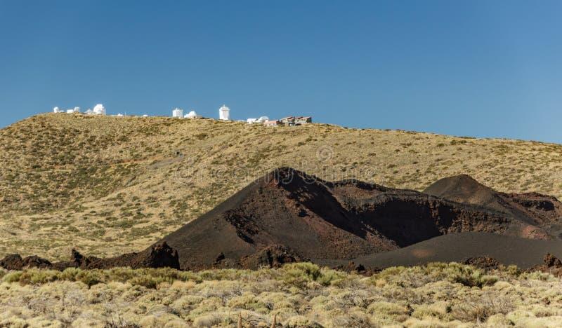 Internationaal waarnemingscentrum in het Nationale Park van Teide Jonge Vulkaan in de voorgrond Winderige dag met heldere blauwe  royalty-vrije stock foto's