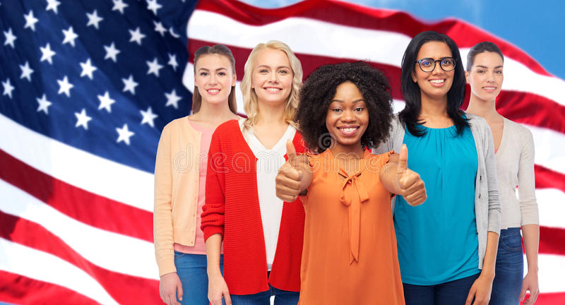 International american women showing thumbs up. Diversity and people concept - international group of happy smiling different women howing thumbs up over royalty free stock images