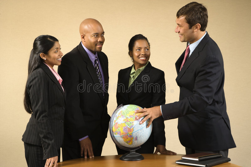 International business. Corporate businesspeople standing around world globe smiling and talking royalty free stock photo