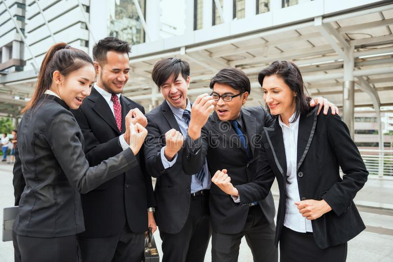 International Business colleague cheer up. International Business colleague celebrate success with arms raised in modern city after project achievement stock photos