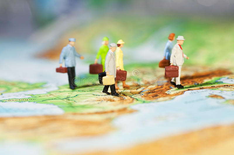 International Business Cooperation. A groupd of miniature businesspeople models walking across a map, low angle and shallw DOF royalty free stock photos
