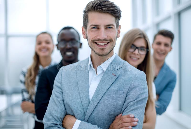 International business people standing with folded arms smiling. Young men with arms folded and friends behind him against a white background royalty free stock photo