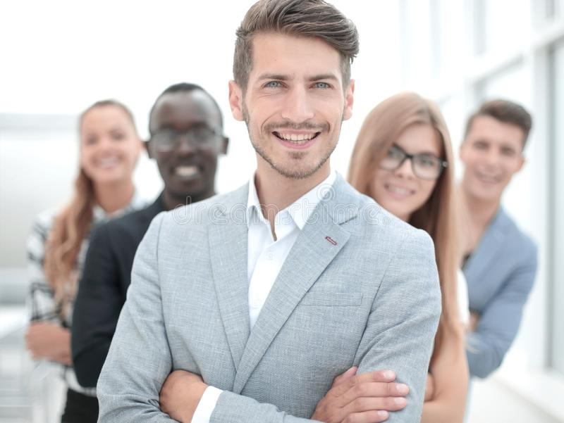 International business people standing with folded arms smiling. Young men with arms folded and friends behind him against a white background royalty free stock photos