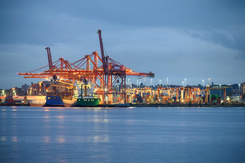 International cargo ship with containers cargo illumination and gantry cranes at port stock photo