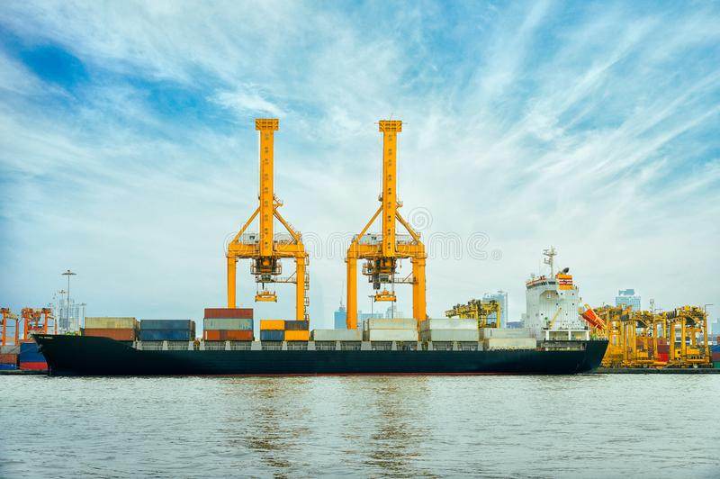 International Container Cargo ship with working crane bridge in shipyard background, logistic import export background and stock images