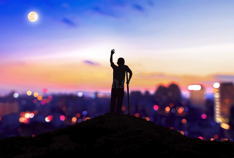 International Day of Persons with Disabilities concept: Silhouette a disabled man standing at mountain city background royalty free stock photography
