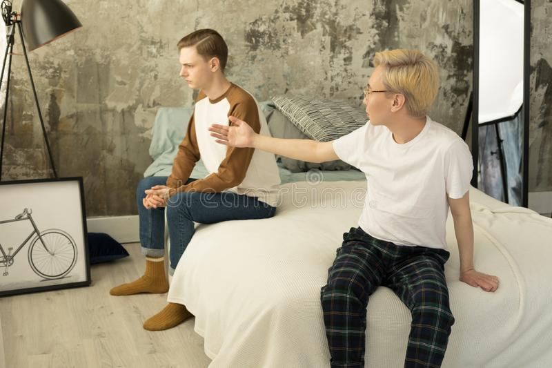 International disgrunled gay couple quarreling each other at homa in the bedroom stock image