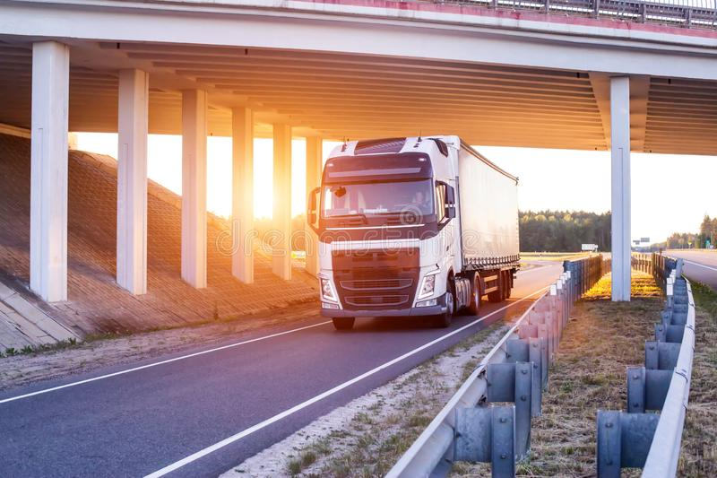 An international driver is carrying goods on a wagon under a bridge. Trucker work concept, work and rest mode, job vacancies, stock image