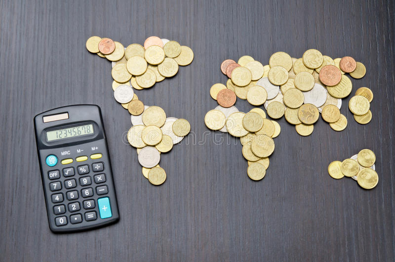 International finance. Office desk with world map made of money coins and calculator royalty free stock photos