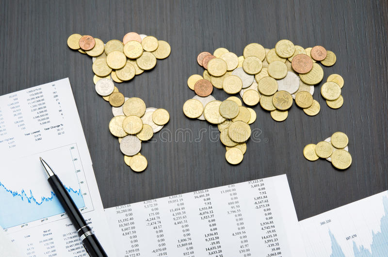 International finance. Office desk with world map made of money coins and report sheets stock photo