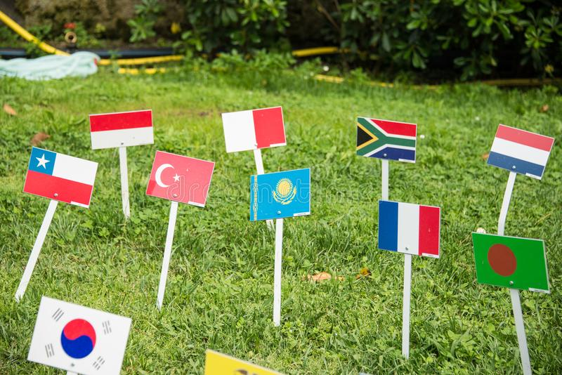 International flags from all over the world all togethrt. International union of different flags on a stick put into the fresh green soil. Many beautiful colors stock image