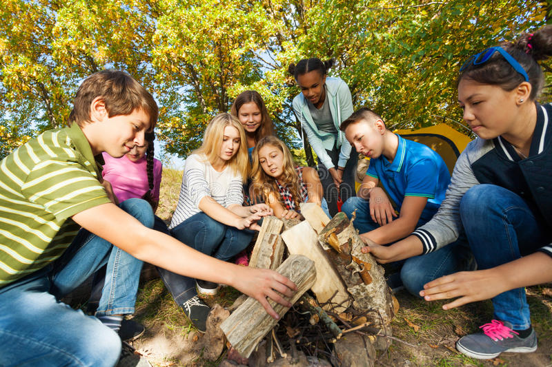 International friends construct bonfire together. Near yellow tent during autumn day in the forest stock image