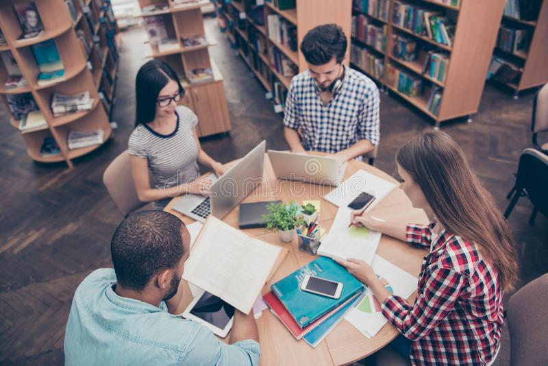 International group of four focused clever young students bookworms studying in the college library, sit and doing assignments royalty free stock photo
