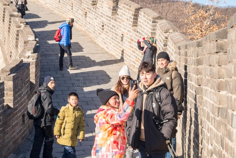 International group of friends on The Great Wall of China taking Selfies and having fun. Dressed in winter clothes, an international group of friends are taking stock photo