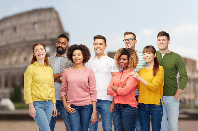 International group of happy people over coliseum. Diversity, travel, tourism and people concept - international group of happy smiling men and women over royalty free stock image