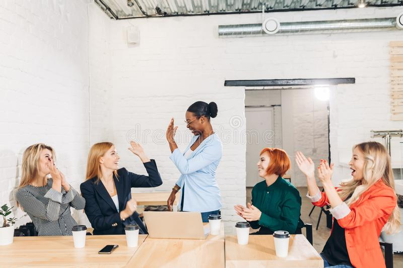 International group of happy women celebrating success at team meeting royalty free stock photo