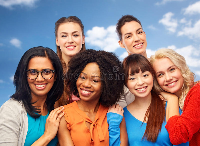 International group of happy women hugging. Diversity, ethnicity and people concept - international group of happy smiling different women hugging over blue sky royalty free stock photography