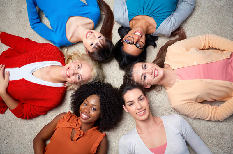 International group of happy women lying on floor. Diversity, race, ethnicity and people concept - international group of happy smiling different women lying on stock photography