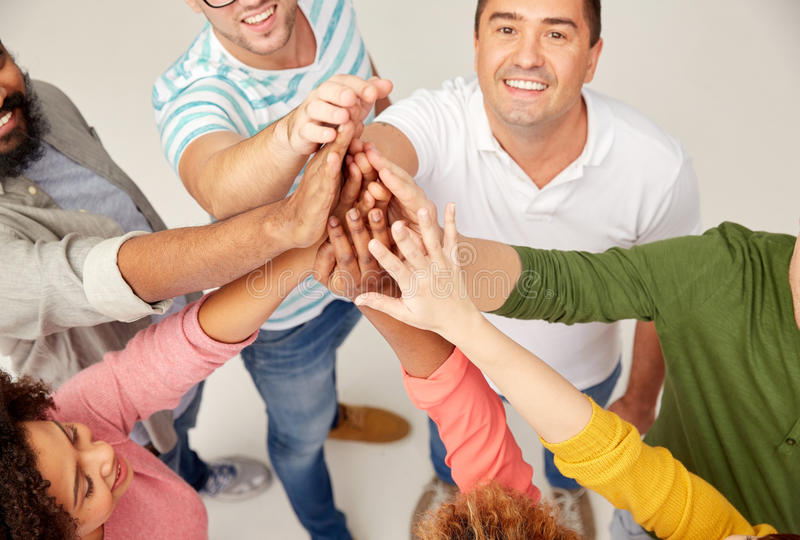 International group of people making high five. Diversity, race, ethnicity, gesture and people concept - international group of happy smiling men and women stock photo