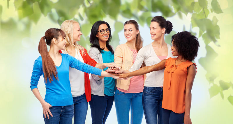 International group of women with hands together. Diversity, race, ethnicity and people concept - international group of happy smiling different women holding royalty free stock image