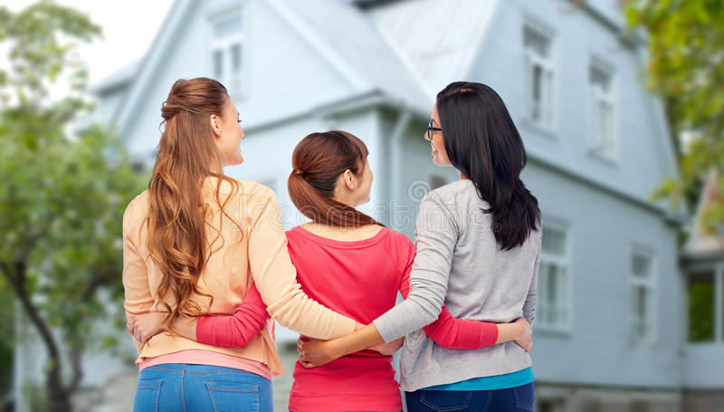 International happy women from back hugging. Diversity, friendship and people concept - international group of happy smiling different women hugging from back royalty free stock image